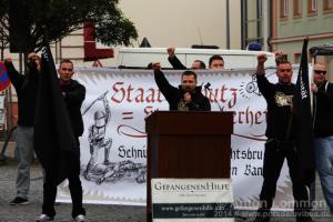 """Maik Eminger hält am 25. Oktober 2014 in Brandenburg an der Havel bei der Kundgebung der neonazistischen """"Gefangenenhilfe"""" eine Rede. Links neben ihm steht Tim Borowski, rechts daneben Philipp Hinzmann"""