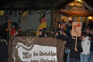 """Lukas Franz trägt das Transparent """"Wir für Deutschland gegen Überfremdung"""" der neonazistischen Kampagne """"Ein Licht für Deutschland"""" am 17. Dezember in Oranienburg."""