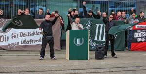 """Tim Borowski (rechts vom Redner_innenpult mit Fahne) auf einer Kundgebung der neonazistischens Kleinstpartei """"Der III. Weg"""" am 18. April 2015 in Brandenburg (Havel)"""