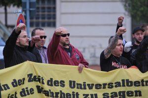 """Tony Schmidt (ganz rechts im Hintergrund) hebt zum Ende der Kundgebung am 25. Oktober 2014 in Brandenburg/Havel die Faust und fordert zusammen mit den restlichen Teilnehmer_innen einen """"Nationalen Sozilismus"""". Vorne am Transparent (mit rotem Pullover) der Neonazi und Totschläger Sascha Lücke."""
